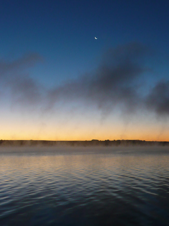 Moon over sunrise on the lake, with lake mist
