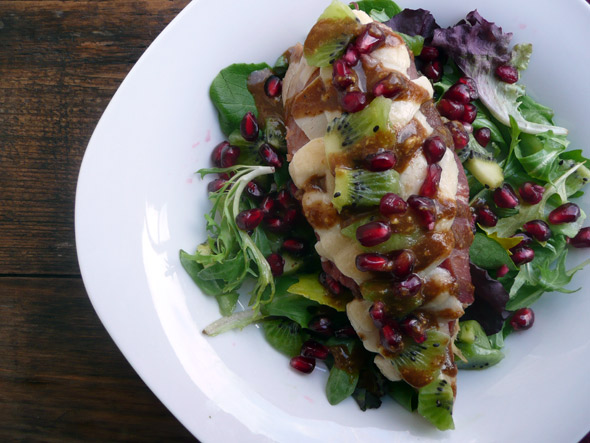 on a bed of greens with Kiwi, Pomegranate, and a Sweet Baslamic Habanero Mustard Drizzle
